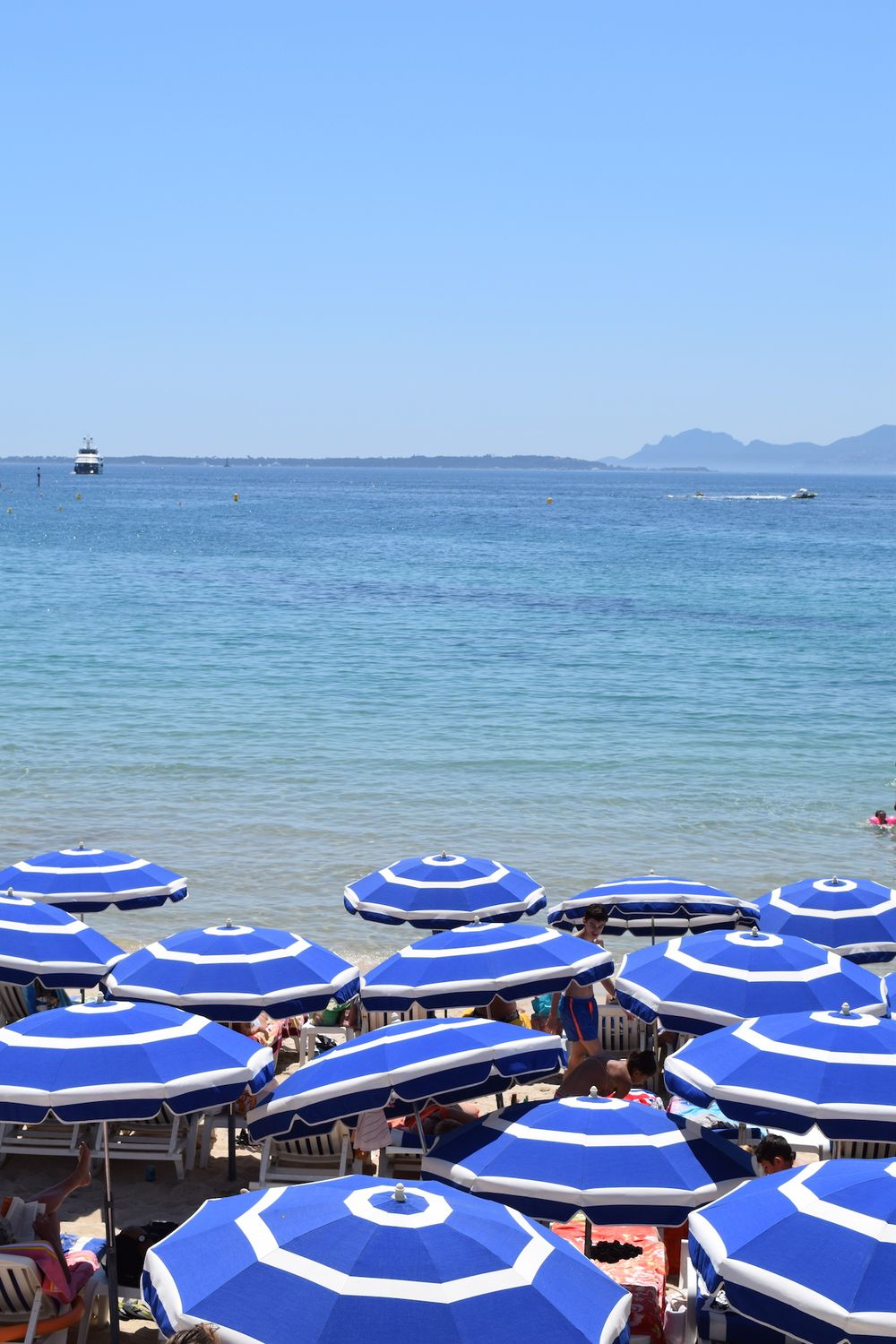 Blue and white umbrellas on beach by Juan-Les-Pins, France