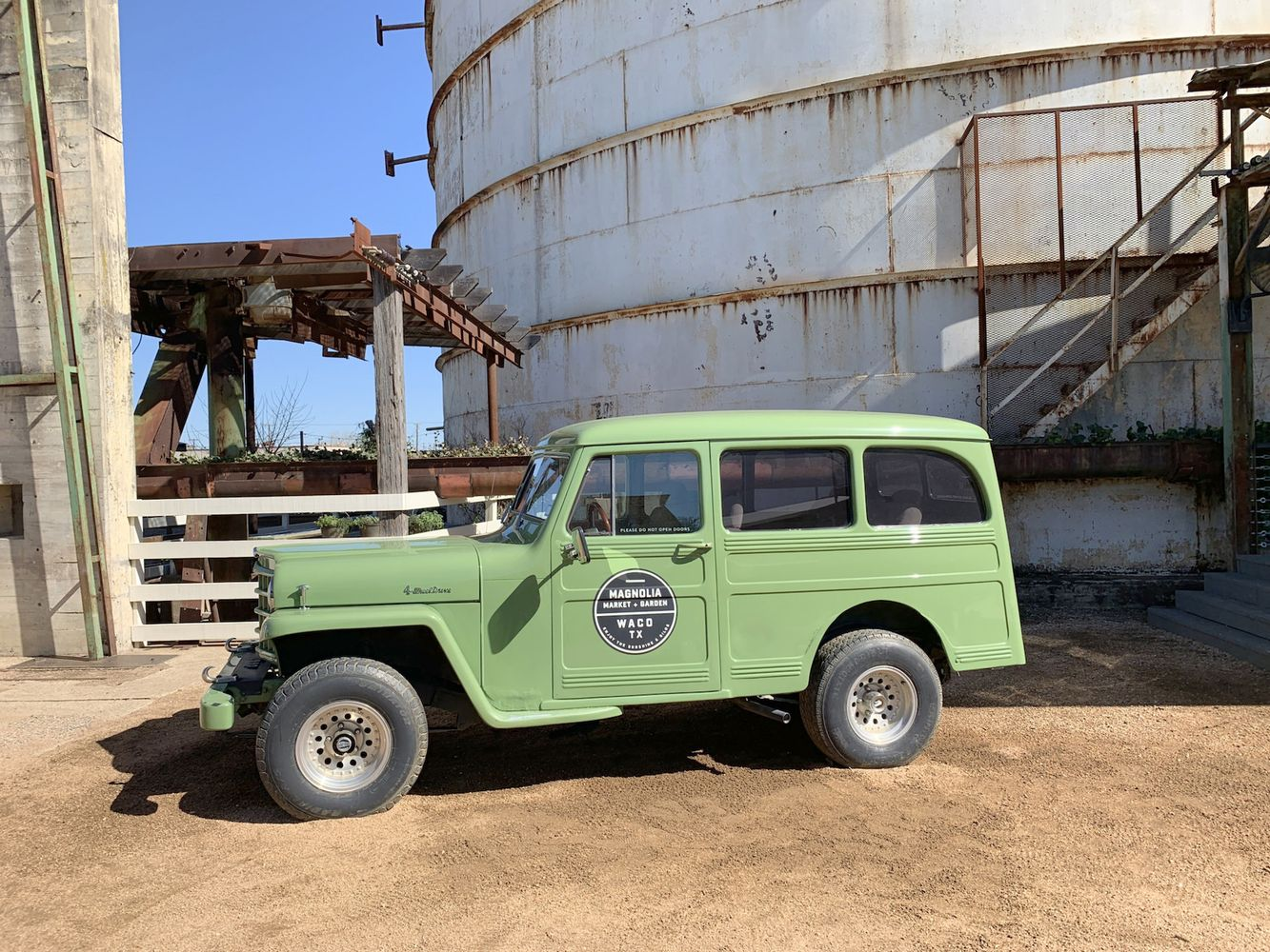 Green Car in front of the Silos at Magnolia Market